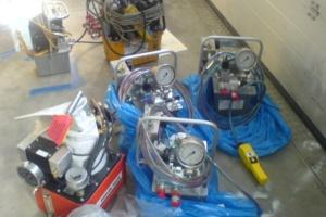 Auch die dreistufige Druckluft-Hydraulikpumpe PA10 (rechts) leistet soviel wie die schwereren Modellen (hier die PA554TWP von Power Team)